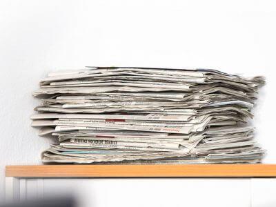 Das Bild zeigt einen Zeitungsstapel. Der Artikel geht der Frage nach, ob der Trend des Clickbaiting auch im Printjournalismus zu schlechten Überschriften führt.