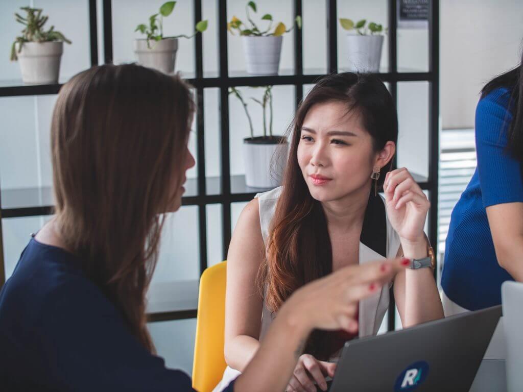 Das Bidl zeigt zwei Frauen im Gespräch. Der Artikel beschreibt wie wichtig die richtige Formulierung von Fragen ist.