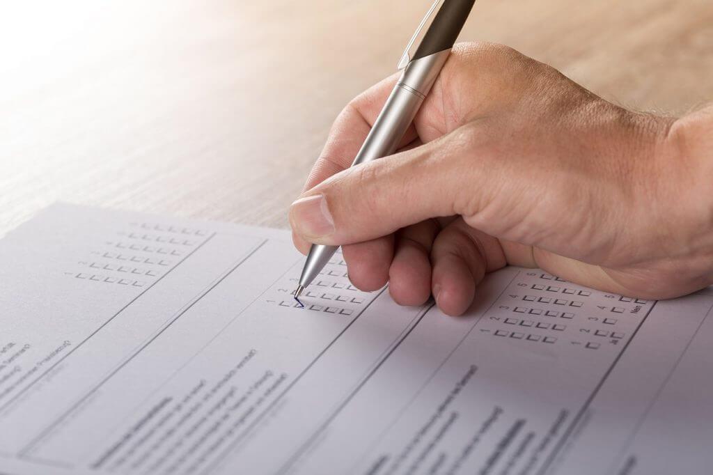 Eine Hand kreuzt einen Fragebogen an. Der Artikel beschreibt wie Befragungen in der Kommunikationsarbeit genutzt werden können.