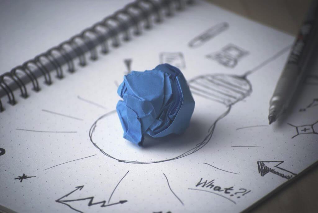Das Bild zeigt eine gezeichnete Glühbirne auf der ein zerknülltes Papier liegt. Der Artikel erklärt, was ein gutes Briefing ausmacht.