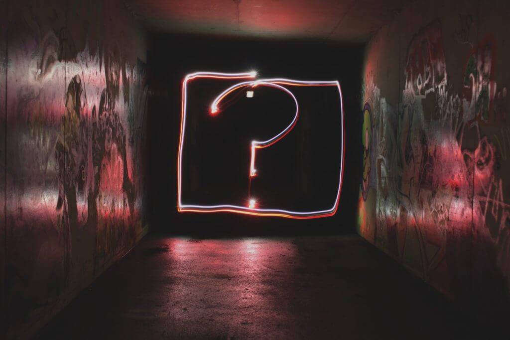 Das Bild zeigt ein leuchtendes Fragezeichen. Der Artikel beschäftigt sich mit den wichtigsten Fragen vor einer Online-Befragung.