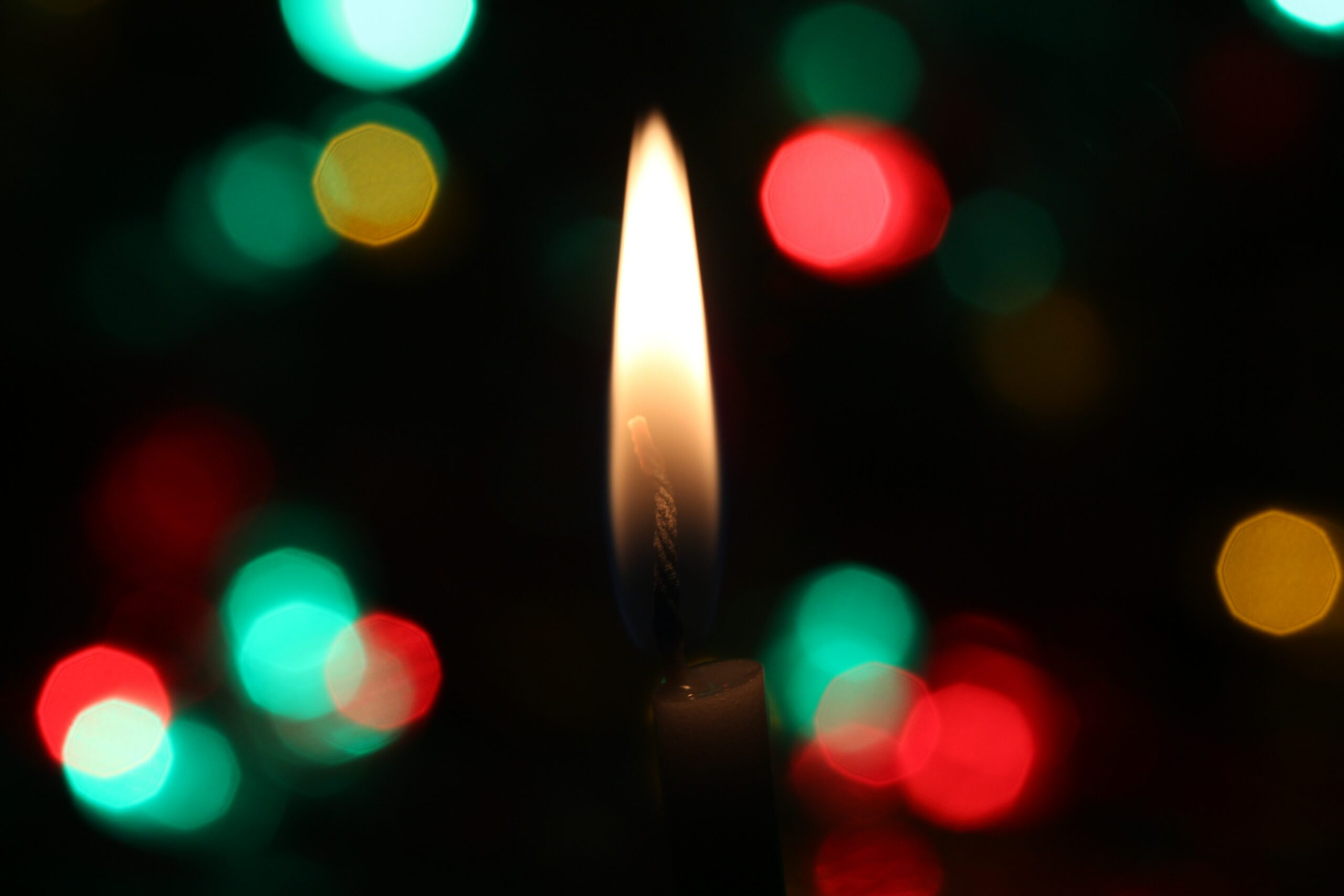 Kerzenflamme vor dunklem Hintergrund. In diesem Artikel erfahren Sie wie Sie die Weihnachtszeit für Pressearbeit nutzen können.