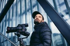 Portraitbild von Mann mit Kamera auf Stativ